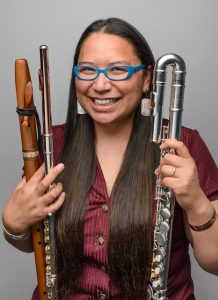 A woman smiles while holding several types of flute