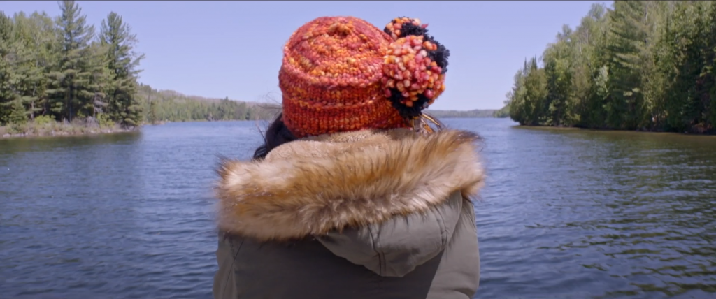 Rear view of a person, wearing a wool hat and a parka, as they look out over water
